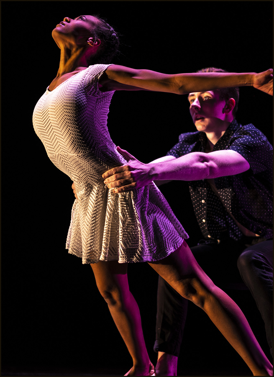 A female dancer with outstretched arms in a light-colored dress being held from behind by a male dancer in dark clothing
