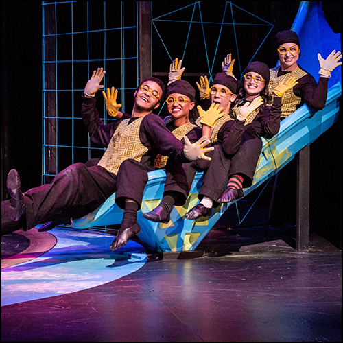 Five student actors in matching brown slacks, gold vests and gloves posing on-stage sliding down a blue slide